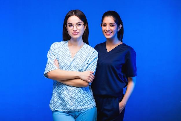 Zespół młodych mieszkańców. lekarz, pielęgniarka i chirurg w niebieskim tle. do celi zagląda grupa studentów medycyny różnych narodowości