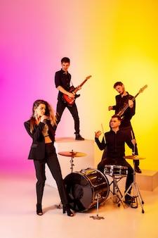 Zespół młodych muzyków kaukaskich występujących w świetle neonowym na gradientowym tle studyjnym
