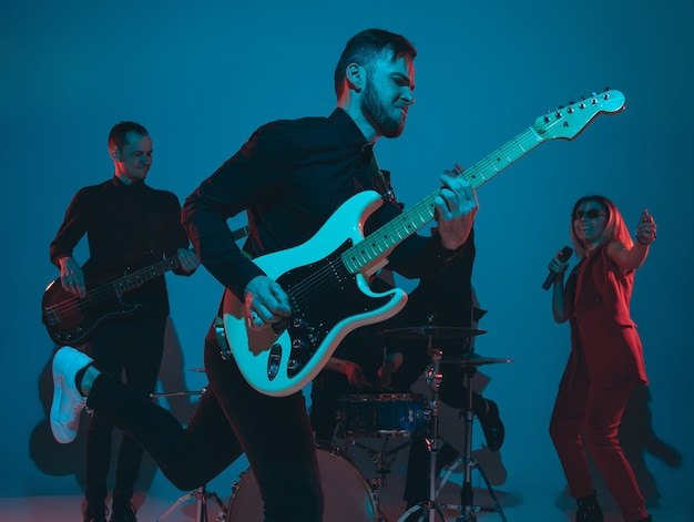 Zespół młodych muzyków kaukaskich występujących w świetle neonowym na niebieskim tle studia
