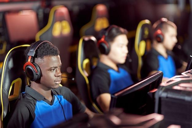 Zespół młodych profesjonalnych graczy cybersportowych w słuchawkach biorących udział w turnieju e-sportowym