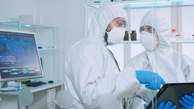 Zespół naukowców w kombinezonie dyskutujący o rozwoju szczepionek patrzący na tablet w wyposażonym laboratorium. lekarz analizujący ewolucję wirusa przy użyciu zaawansowanych technologii do badania leczenia przeciw covid19