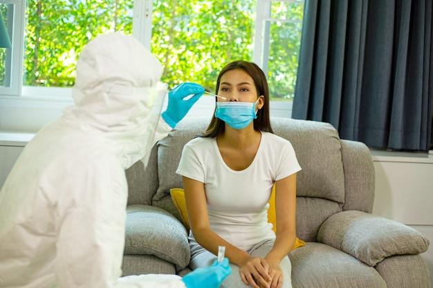 Zespół personelu medycznego ppe przechowuje próbkę przed chorobą pacjenta. odwiedź chorą kobietę w domu, aby odizolować i oddzielić ją do innego miejsca.