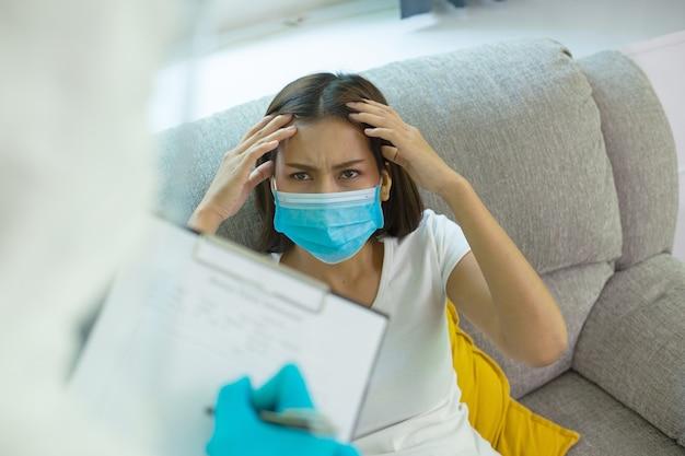 Zespół personelu medycznego ppe trzymający tablicę kontrolną na notatkę z długopisem w celu sprawdzenia choroby pacjenta. odwiedź chorą kobietę w domu, aby odizolować i oddzielić do innego miejsca.