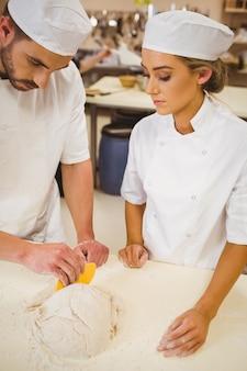 Zespół piekarzy przygotowuje ciasto
