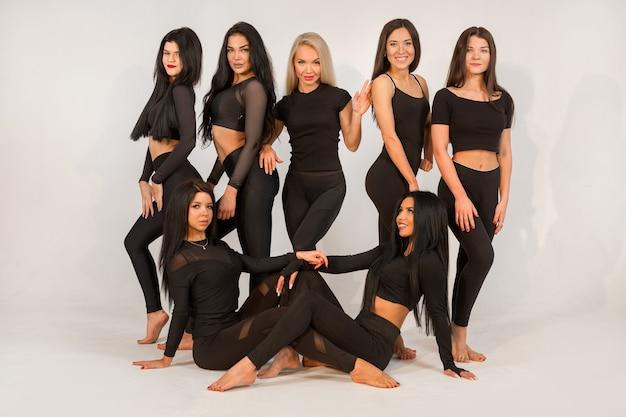 Zespół pięknych młodych kobiet w czarnych dresach na białym tle