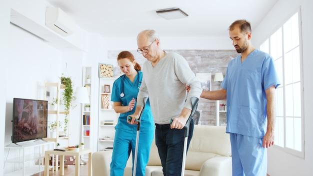 Zespół pielęgniarek lub pracowników socjalnych pomagający starszemu niepełnosprawnemu mężczyźnie wychodzić o kulach z pokoju w domu opieki.