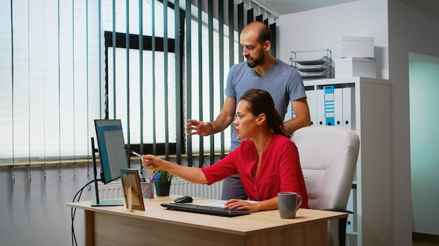 Zespół poszukujący najlepszego rozwiązania przed komputerem w nowoczesnym pomieszczeniu biurowym. współpracownicy omawiają pracę w miejscu pracy w osobistej firmie korporacyjnej, pisząc na klawiaturze komputera, wskazując na pulpit