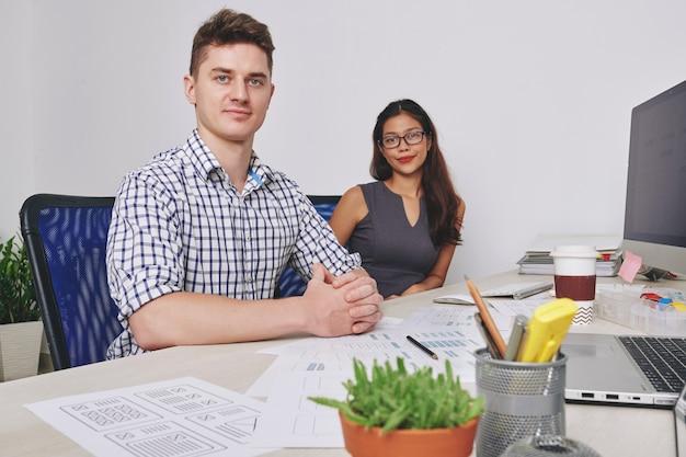 Zespół pozytywnych, pewnych siebie młodych projektantów ux pracujących nad projektem przy biurku