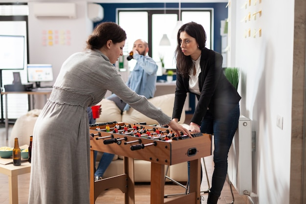 Zespół pracowników grających w zabawną grę po pracy w biurze podczas jedzenia i picia. różnorodni koledzy korzystający z gry w piłkarzyki piłka nożna piłka nożna rozrywka z pizzą i piwem