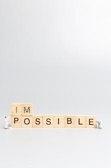 Zespół pracowników miniaturowych ludzi na niemożliwe słowo w drewnianych literach alfabetu z prefiksem un przekreślonym, pozostawiając słowo możliwe