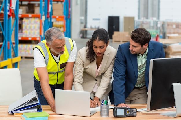 Zespół pracowników pracuje na biurku z komputerami