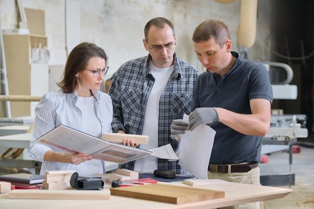 Zespół pracowników warsztatów obróbki drewna dyskutuje.