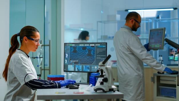 Zespół pracujący nad opracowaniem nowej szczepionki w nowocześnie wyposażonym laboratorium, kobieta pisząca na komputerze. grupa naukowców biochemicznych badających ewolucję wirusów przy użyciu zaawansowanych technologii do badania leczenia