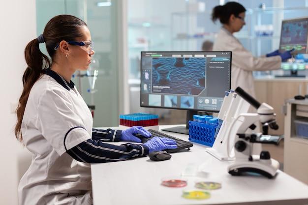 Zespół pracujący nad opracowaniem nowej szczepionki w nowocześnie wyposażonym laboratorium, piszący na komputerze. naukowcy badający ewolucję szczepionek w laboratorium medycznym przy użyciu zaawansowanych technologicznie narzędzi chemicznych do badań naukowych.