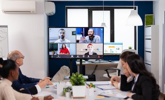 Zespół pracujący w ramach grupowej rozmowy wideo dzieli się pomysłami, przeprowadza burze mózgów, negocjuje, korzysta z wideokonferencji. ludzie biznesu rozmawiają z kamerą internetową, czy konferencje online biorą udział w internetowej burzy mózgów, biurach na odległość?