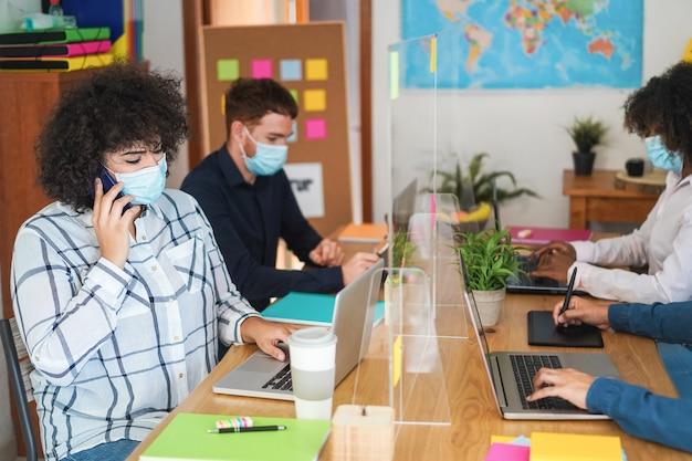 Zespół pracujący wewnątrz nowoczesnego biura w maskach
