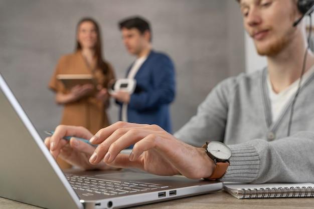 Zespół profesjonalnych ludzi korzystających z laptopa i zestawu słuchawkowego wirtualnej rzeczywistości