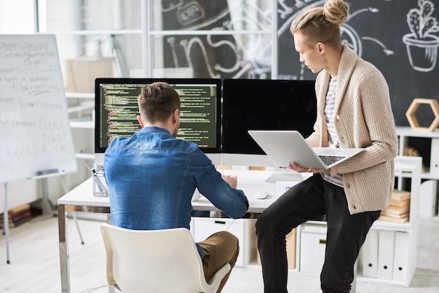 Zespół programistów omawiający kod komputerowy
