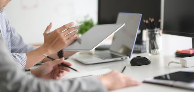 Zespół programistów stron internetowych ux pracuje nad swoim projektem wraz z tabletem i laptopem