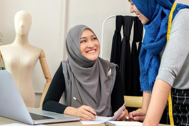 Zespół projektantów mody muzułmańskiej kobiety pracującej w sklepie krawieckim