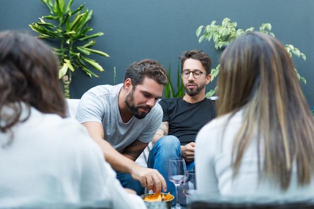 Zespół przyjaciół delektujących się winem i przekąskami