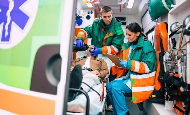 Zespół ratownictwa medycznego ze starszym pacjentem w karetce