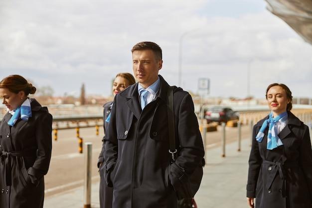 Zespół samolotu chodzenie na chodniku w pobliżu nowoczesnego lotniska. młode uśmiechnięte kobiety i mężczyzna noszą mundur. stewardesa i stewardesy. praca w zespole. cywilne lotnictwo komercyjne. koncepcja podróży lotniczych