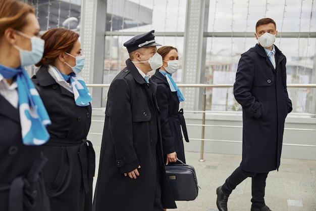 Zespół samolotu spaceru w nowoczesnym lotnisku. kobiety i mężczyźni noszą mundury i maski medyczne. pilot, stewardesa i stewardesy. praca w zespole. cywilne lotnictwo komercyjne. koncepcja podróży lotniczych
