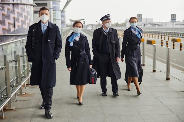 Zespół samolotu spaceru z bagażem na chodniku w pobliżu lotniska. kobiety i mężczyźni noszą mundury i maski medyczne. pilot, stewardesa i stewardesy. praca w zespole. lotnictwo cywilne. koncepcja podróży lotniczych
