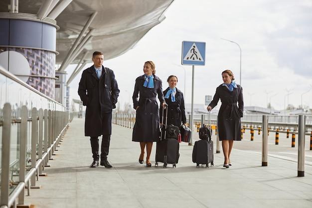 Zespół samolotu spaceru z bagażem na chodniku w pobliżu lotniska. młode uśmiechnięte kobiety i mężczyzna noszą mundur. stewardesa i stewardesy. praca w zespole. cywilne lotnictwo komercyjne. koncepcja podróży lotniczych