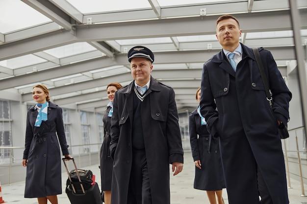 Zespół samolotu spacerujący z bagażem w pobliżu wejścia na nowoczesne lotnisko. uśmiechnięte kobiety i mężczyźni noszą mundury. pilot, stewardesa i stewardesy. praca w zespole. cywilne lotnictwo komercyjne. koncepcja podróży lotniczych