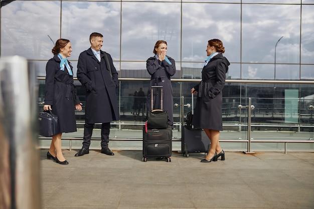 Zespół samolotu stojący i rozmawiający w pobliżu nowoczesnego lotniska. młode uśmiechnięte kobiety i mężczyzna z bagażem nosić mundur. stewardesa i stewardesy. praca w zespole. cywilne lotnictwo komercyjne. koncepcja podróży lotniczych