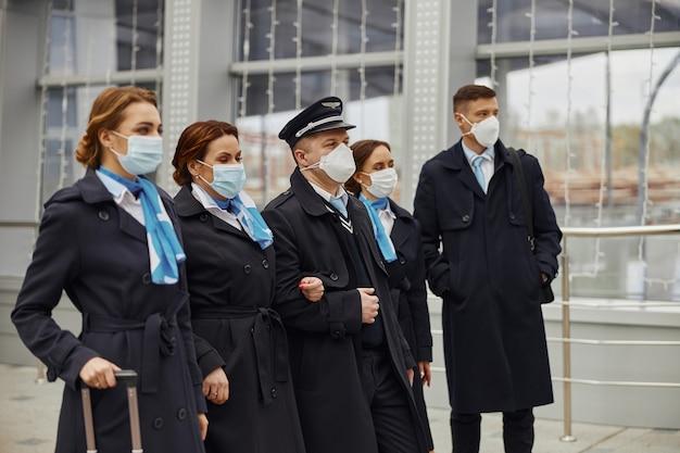 Zespół samolotu stojący w nowoczesnym lotnisku. kobiety i mężczyźni noszą mundury i maski medyczne. pilot, stewardesa i stewardesy. praca w zespole. cywilne lotnictwo komercyjne. koncepcja podróży lotniczych