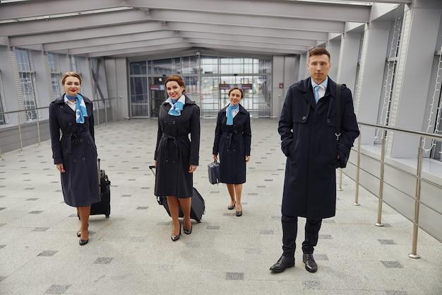Zespół samolotu stojący z bagażem w pobliżu wejścia na nowoczesne lotnisko. uśmiechnięte młode kobiety i mężczyzna noszą mundur. stewardesa i stewardesy. praca w zespole. cywilne lotnictwo komercyjne. koncepcja podróży lotniczych