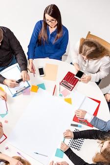 Zespół siedzący za biurkiem, sprawdzający raporty, rozmawiając widok z góry
