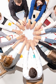 Zespół siedzący za biurkiem, sprawdzający raporty, rozmawiający i łączący ręce. widok z góry. biznesowa koncepcja współpracy, pracy zespołowej, spotkania