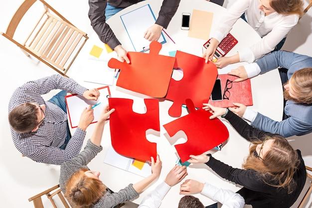 Zespół siedzący za biurkiem, sprawdzający raporty, rozmawiający, wspólnie zbierając puzzle. widok z góry.