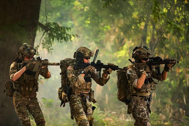 Zespół sił specjalnych. karabin szturmowy żołnierza z tłumikiem. snajper w lesie.