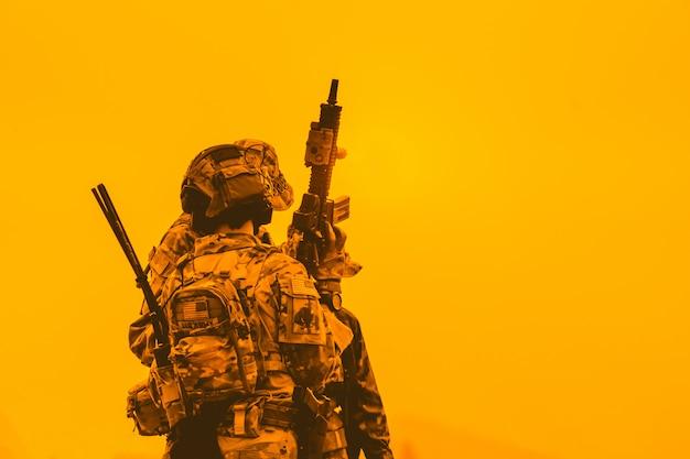 Zespół sił specjalnych. starszy karabin szturmowy z tłumikiem. sylwetka żołnierzy akcji trzymać broń. koncepcja wojskowa i niebezpieczeństwa.