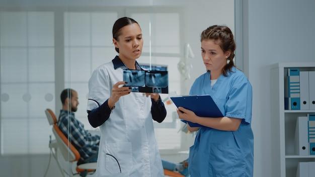 Zespół stomatologów ortodontów omawiający pielęgnację zębów pacjenta