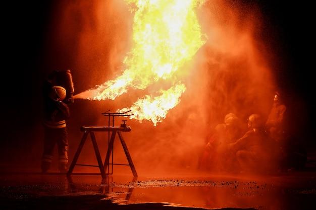 Zespół strażaków ćwiczy gaszenie płonącego ognia w nocy.