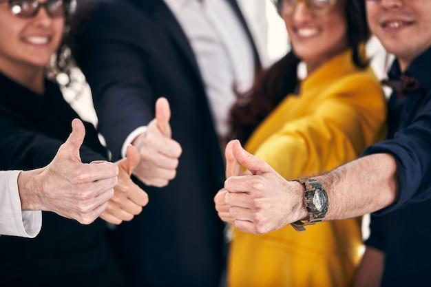 Zespół szczęśliwy biznes. grupa wesołych ludzi biznesu w casual, stojących blisko siebie i pokazujących kciuki do góry. selektywna ostrość