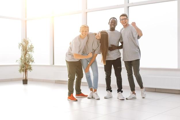 Zespół szczęśliwych młodych ludzi stojących razem