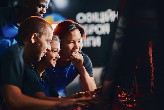 Zespół szczęśliwych profesjonalnych graczy cybersportowych patrzących na ekran komputera i czujących się podekscytowany i szczęśliwy