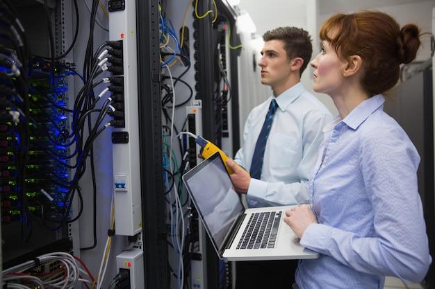 Zespół techników za pomocą cyfrowego analizatora kabla na serwerach