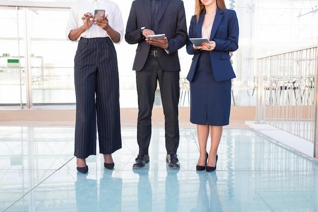 Zespół trzech osób korzystających z urządzeń cyfrowych w holu biurowym