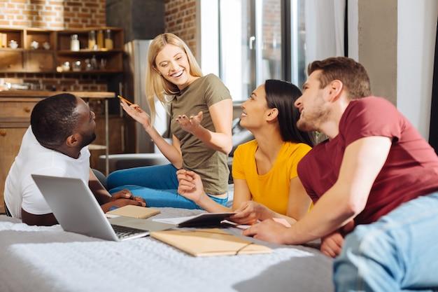 Zespół w pracy. czterech optymistycznych, kreatywnych, zadumanych studentów wypoczywa na łóżku, komunikując się i gestykulując piękna dziewczyna