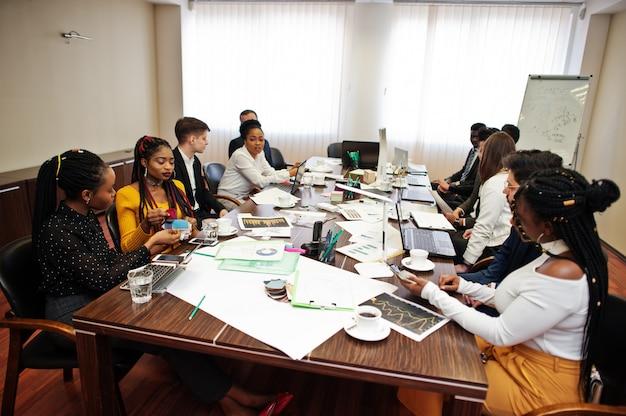 Zespół wielorasowego biznesu adresujący spotkanie wokół stołu sali konferencyjnej.