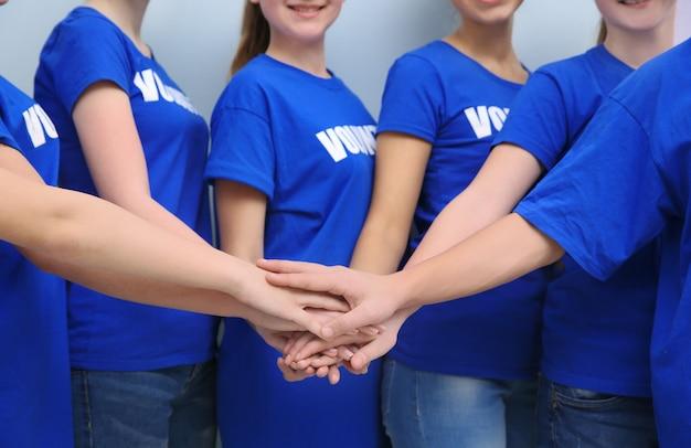 Zespół wolontariuszy składających ręce jako symbol jedności, na kolor
