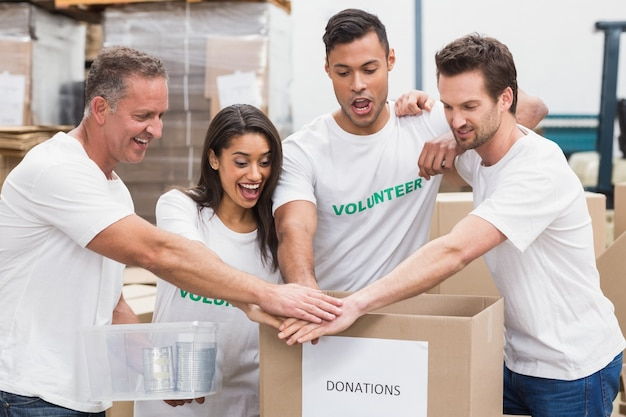 Zespół wolontariuszy trzymając się za ręce na polu darowizn